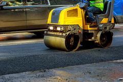 Urban road is under construction, asphalting of yellow roller. Urban road is under construction, asphalting in progress, fragment of yellow roller Royalty Free Stock Photos