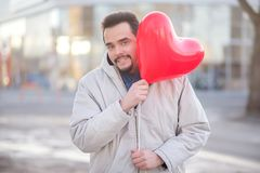 Urban romance: young man with a hipster beard waiting for a date and jokingly looking out from the heart shaped air balloon royalty free stock photo