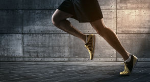 Urban runner. Close up of urban runner's legs run on the street with copy space Stock Photos