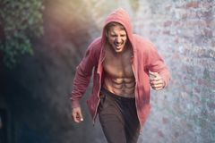 Urban runner in hoodie in the city park. Doing high intensity training Royalty Free Stock Photos