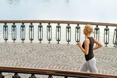 Urban running. A young woman running on bridge in urban environment stock photos