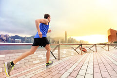 Urban running man runner in Hong Kong city skyline. Caucasian man working out jogging on the promenade of Victoria Harbor in HongKong, China, in afternoon Royalty Free Stock Photos