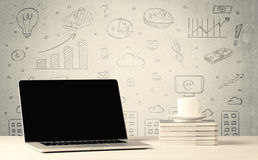Urban sales graphs and laptop on desk. An open laptop on a white office desk with flower, coffee, books in front of wall background full of financial business Royalty Free Stock Photo