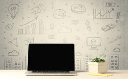 Urban sales graphs and laptop on desk. An open laptop on a white office desk with flower, coffee, books in front of wall background full of financial business Stock Photography