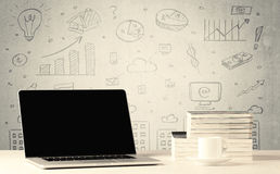 Urban sales graphs and laptop on desk. An open laptop on a white office desk with flower, coffee, books in front of wall background full of financial business Stock Photo