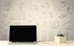 Urban sales graphs and laptop on desk. An open laptop on a white office desk with flower, coffee, books in front of wall background full of financial business Stock Photos