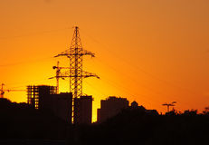 Urban  sunset. High voltage electricity pylon and construction project silhouette over sunset Stock Photography