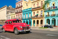 Urban scene with colorful buildings and old car in Havana. HAVANA,CUBA - DECEMBER 13,2017 : Urban scene with colorful buildings and old car in Havana Stock Photos