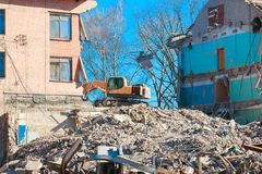 Urban scene. Dismantling of a house. Building demolition and crashing by machinery for new construction. Industry.  Stock Image