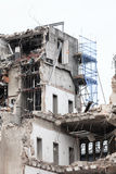 Urban scene. Dismantling of a house. Building demolition and crashing by machinery for new construction. Stock Images