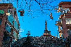 Urban scene. Dismantling of a house. Building demolition and crashing by machinery for new construction. Industry.  Royalty Free Stock Image