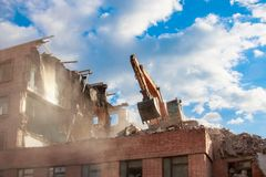 Urban scene. Dismantling of a house. Building demolition and crashing by machinery for new construction. Industry.  Royalty Free Stock Photos