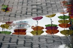 Colorful umbrellas reflected on a rain puddle on the pavement royalty free stock photos