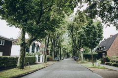 Urban scene of street with green trees and buildings. In hamburg, germany stock image