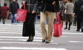 Urban shoppers. Image of the two women with bags crossing the street in a big city Stock Images