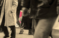 Urban shopping abstract. Selective focus on two shopping bags between the crowd legs in motion-selective sepia tones Stock Images