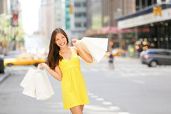 Urban shopping woman in New York City street. With yellow taxi cab. Beautiful happy summer shopper holding shopping bags walking outside smiling. Multiracial Royalty Free Stock Photo