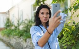 Urban shot of cute stylish European woman making funny face while posing for selfie. Selective focus. Lifestyle and people concept. Urban shot of cute stylish royalty free stock photos