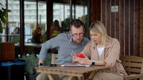 Couple using modern gadgets in city. Urban shot of a young boyfriend and girlfriend using modern devices and talking. Blonde woman typing on her smartphone and stock video