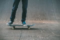 Urban skater sport hobby lifestyle man ramp. Urban skater. Sport hobby and lifestyle. Man on skateboard. Legs in jeans shot. Skate park ramp. Copy space royalty free stock image