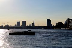 Urban skyline and river facing the sun royalty free stock images