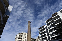 City skyscape. Wispy white clouds against deep blue sky is surrounded by high-rise buildings and historic chimney to form an urban skyscape Royalty Free Stock Photography