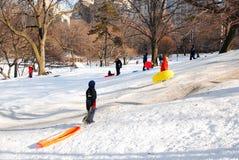 Urban Sledding. Children enjoy a snow day sledding on Pilgrim Hill in New York`s Central Park Royalty Free Stock Image