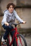 Urban som cyklar - tonårs- pojke och cykel i stad Arkivfoton
