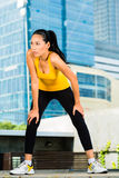 Urban sports - fitness in Asian or Indonesian city. Urban sports - Asian Indonesian woman doing fitness in the city on a beautiful summer day Stock Images