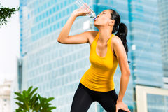 Urban sports - fitness in Asian or Indonesian city. Urban sports - Asian Indonesian woman doing fitness in the city on a beautiful summer day Royalty Free Stock Photo