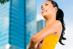 Urban sports - fitness in Asian or Indonesian city. Urban sports - Asian Indonesian woman doing fitness in the city on a beautiful summer day Royalty Free Stock Images