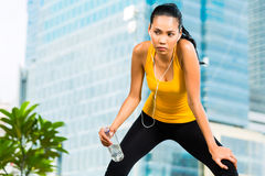 Urban sports - fitness in Asian or Indonesian city. Urban sports - Asian Indonesian woman doing fitness in the city on a beautiful summer day Royalty Free Stock Photography