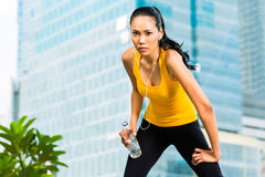 Urban sports - fitness in Asian or Indonesian city. Urban sports - Asian Indonesian women doing fitness in the city on a beautiful summer day Stock Photo