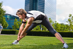 Urban sports - fitness in the city. Urban sports - young man is doing warming up before running in the city on a beautiful summer day Royalty Free Stock Image