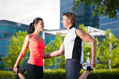 Urban sports - fitness in the city. Urban sports - young couple is doing warming up before running in the city on a beautiful summer day Stock Images