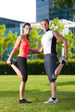 Urban sports - fitness in the city. Urban sports - young couple is doing warming up before running in the city on a beautiful summer day Royalty Free Stock Images