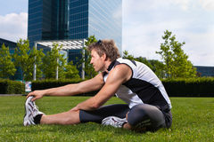 Urban sports - fitness in the city. Urban sports - young man is doing warming up before running in the city on a beautiful summer day Stock Photography