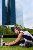 Urban sports - fitness in the city. Urban sports - young man is doing warming up before running in the city on a beautiful summer day Stock Photos