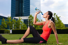 Urban sports - fitness in the city. On a beautiful summer day; a woman is drinking water Stock Image