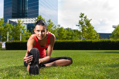 Urban sports - fitness in the city. Urban sports - young woman is doing warming up before running in the city on a beautiful summer day Royalty Free Stock Photos