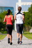 Urban sports - fitness in the city. Urban sports - couple jogging for fitness in the city on a beautiful summer day Stock Images