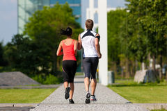 Urban sports - fitness in the city. Urban sports - couple jogging for fitness in the city on a beautiful summer day Stock Photos