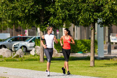 Urban sports - fitness in the city. Urban sports - couple jogging for fitness in the city on a beautiful summer day Stock Photo