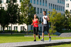 Urban sports - fitness in the city. Urban sports - couple jogging for fitness in the city on a beautiful summer day Royalty Free Stock Image