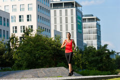 Urban sports - fitness in the city. Urban sports - young woman jogging for fitness in the city on a beautiful summer day Royalty Free Stock Images