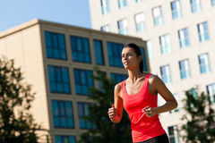 Urban sports - fitness in the city. Urban sports - young woman jogging for fitness in the city on a beautiful summer day Royalty Free Stock Photos