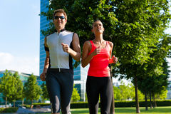 Urban sports - fitness in the city. Urban sports - couple jogging for fitness in the city on a beautiful summer day Royalty Free Stock Images
