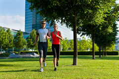 Urban sports - fitness in the city. Urban sports - couple jogging for fitness in the city on a beautiful summer day Stock Image