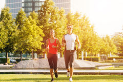 Urban sports - running fitness in the city. Urban sports - couple running or jogging for fitness in the city on beautiful summer day Royalty Free Stock Photography