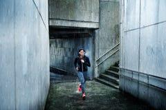 Urban sporty woman running on winter under the rain Stock Photography